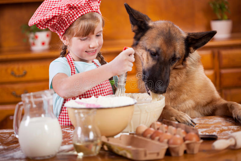 Funny picture of a little girl that blurs the dough ,and German royalty free stock photos