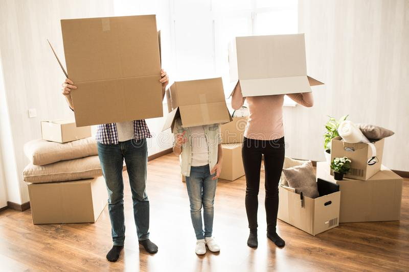 Funny picture of three people that have put boxes on their heads. They are platying some game. This people have lots of stock photo