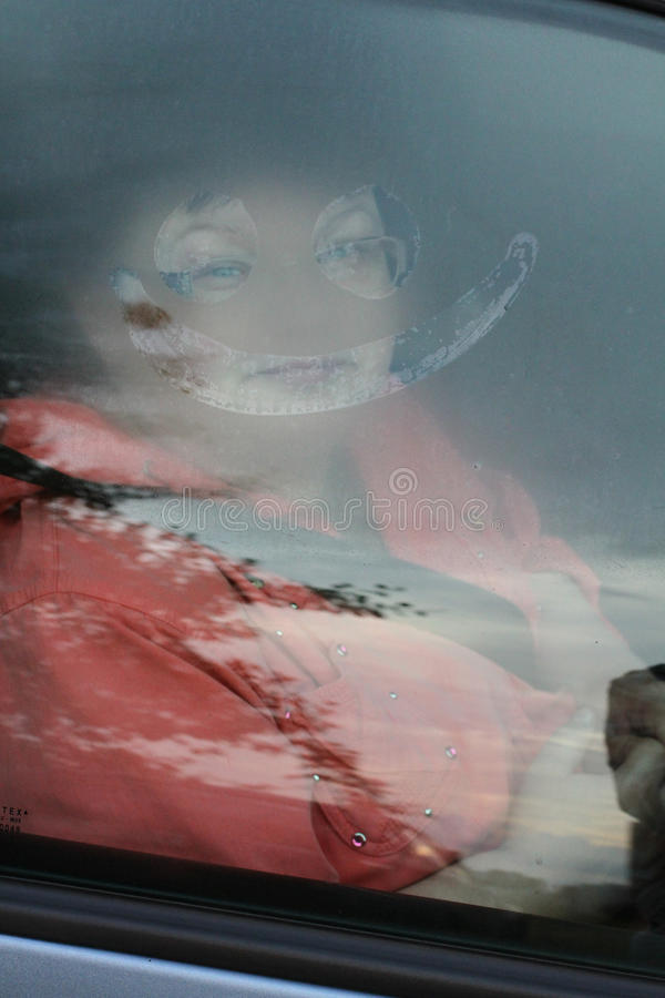 Funny picture of woman sitting on the car. Smile on the window royalty free stock photos