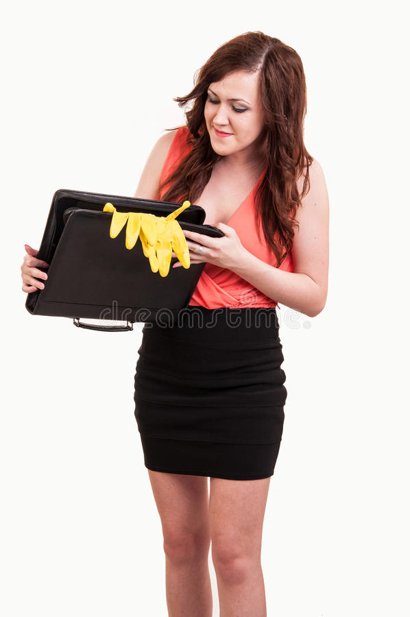 funny picture of young business woman trying to close her briefcase after she put in it yellow rubber gloves royalty free stock images