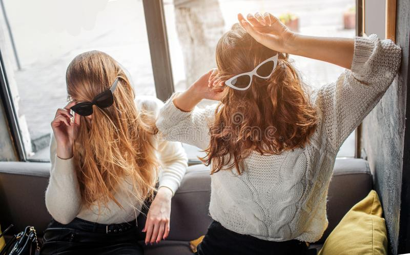 Funny picture of young women holding singlasses on head with hair. They pose and have fun. royalty free stock photography