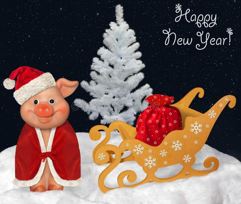 Funny pig near the sleigh. The merry pig in Santa Claus red hat is next to sleigh with a bag of Christmas gifts in the winter forest. Happy New Year royalty free stock images