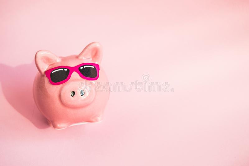 Funny piggy Bank in sunglasses on pink background, sunlight, copy space, money saving concept for summer vacation royalty free stock photography