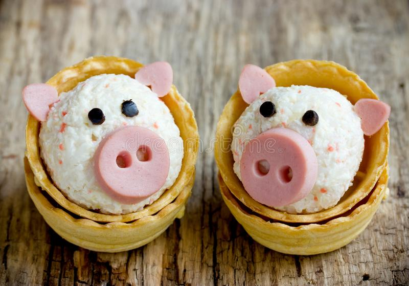 Funny pigs shaped snack tartlets stuffed with rice, surimi crab sticks, garlic and mayonnaise stock images