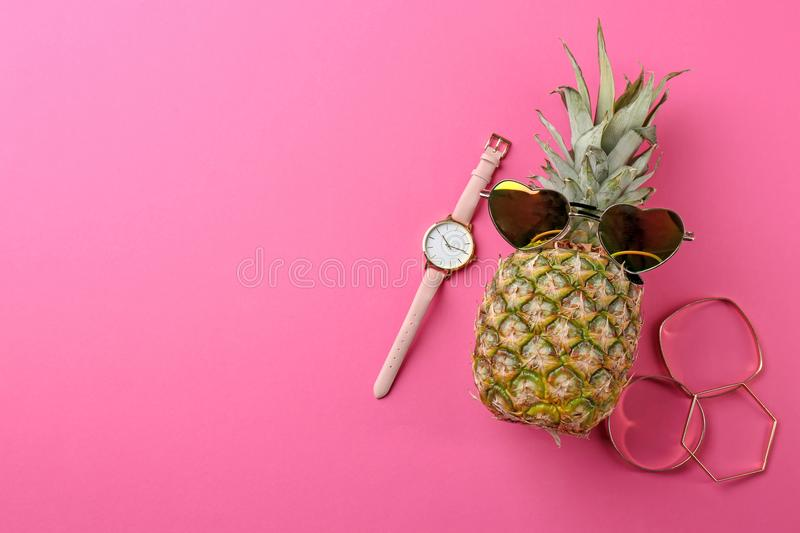 Funny pineapple with sunglasses, bracelets. And watch on color background royalty free stock image