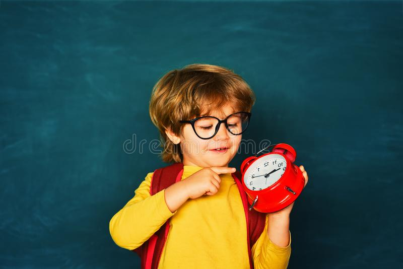 Funny pipil. Back to school. Alarm clock anxiety. Late. Kid boy holding clock alarm. stock photography