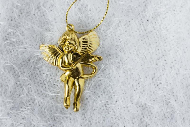 Funny plastic angel as Christmas tree decorations. Funny gold plastic angel as Christmas tree decorations stock image