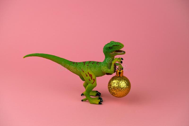 Plastic toy dinosaur with golden christmas ball on a soft pink background. Funny plastic toy dinosaur with golden christmas ball on a soft pink background stock image