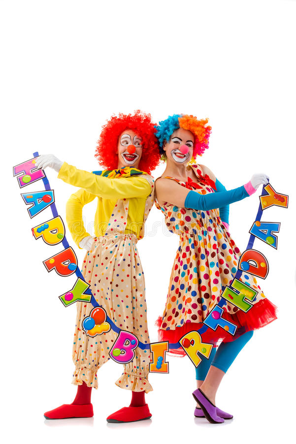 Funny playful clown. Two funny playful clowns holding Happy birthday garland and smiling. Woman looking at camera, men looking at the woman, isolated on white royalty free stock photos