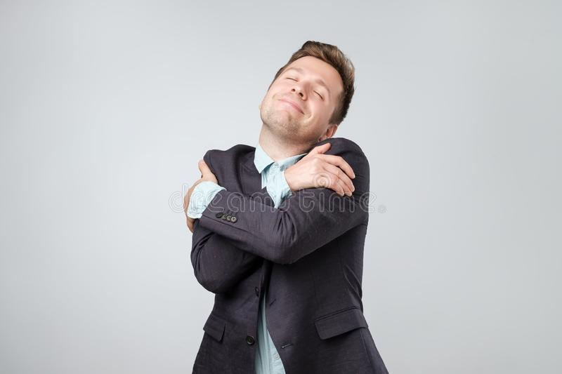 Funny playful european guy in suit cuddling himself and smiling from pleasure, closing eyes and dreaming royalty free stock photos