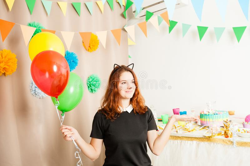 Animator for children`s holiday. Funny playful girl animator in costume of cat holding colorful balls on the birthday party stock photography