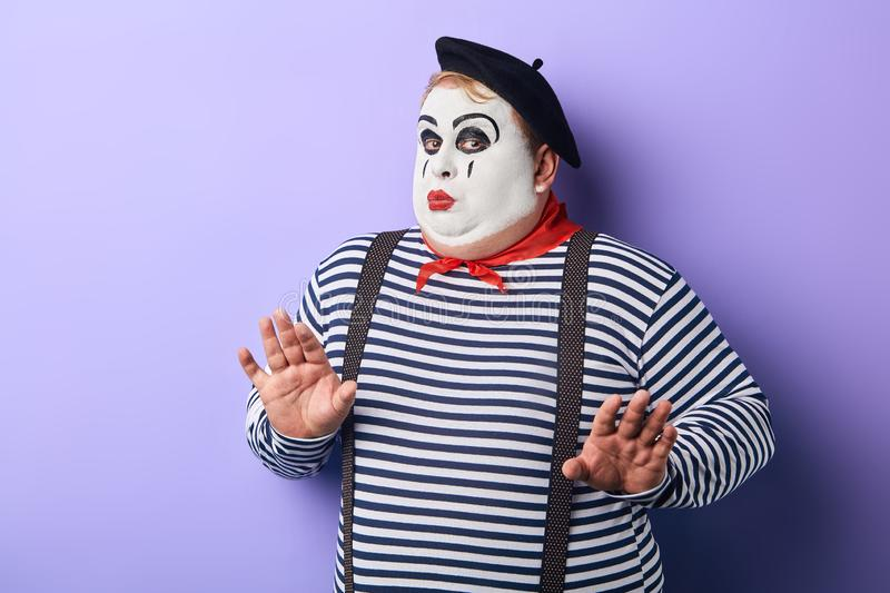 Funny plump mime in stiped clothes asking not to worry royalty free stock images