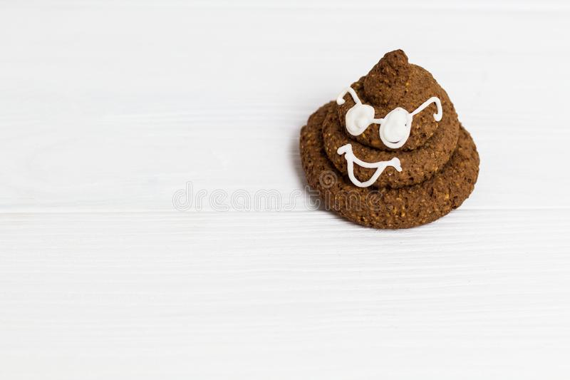 Funny poop emoji chocolate cookie with white decor and glasses. Cute food dessert in right corner. Free place for text. Copyspace. stock photography