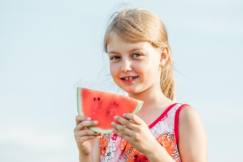 Funny portrait of adorable blonde little girl eating watermelon stock photo