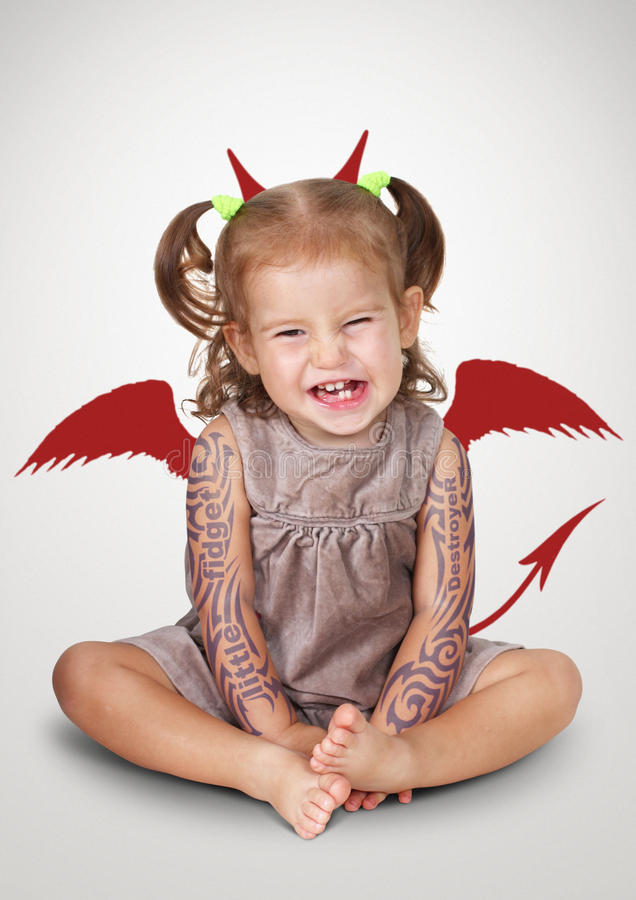 Funny portrait of bad child with tatoo and devil horns, disobedi royalty free stock images