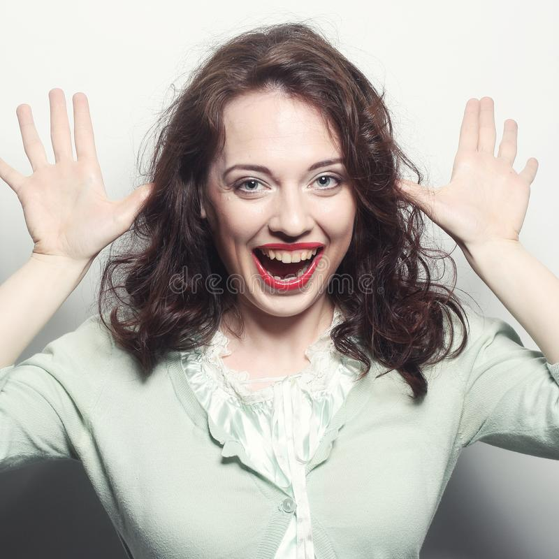 Funny portrait of beauty girl. She is making horns or big bunny ears from her hands, isolated on white royalty free stock photography