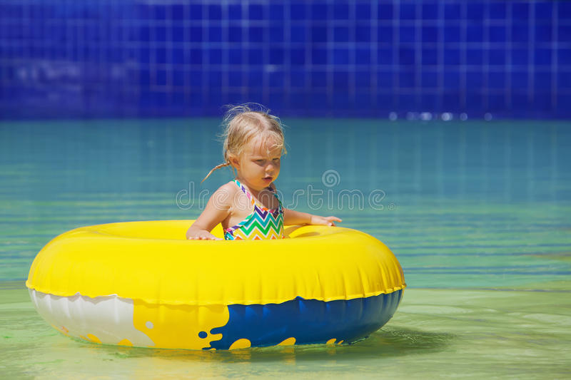 Funny portrait of cheerful baby girl swimming in water park. Funny portrait of cheerful baby girl swimming with fun on yellow tube in aqua park pool. Healthy royalty free stock images