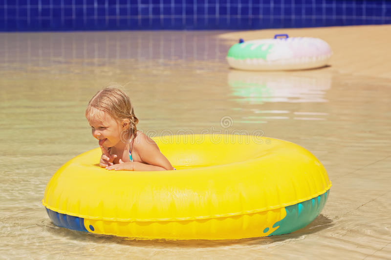 Funny portrait of cheerful baby girl swimming in water park. Funny portrait of cheerful baby girl swimming with fun on yellow tube in aqua park pool. Healthy stock image