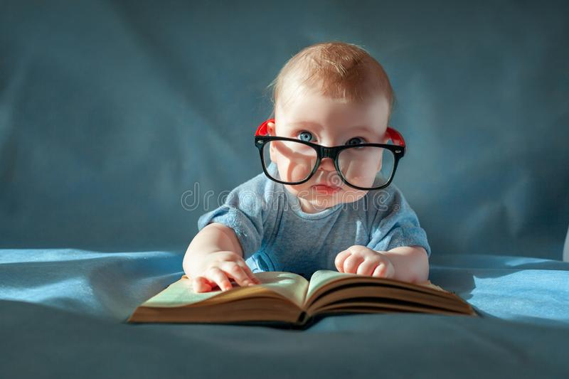Funny portrait of cute baby in glasses. The baby lies on his stomach and reads an old book on a blue background royalty free stock photos