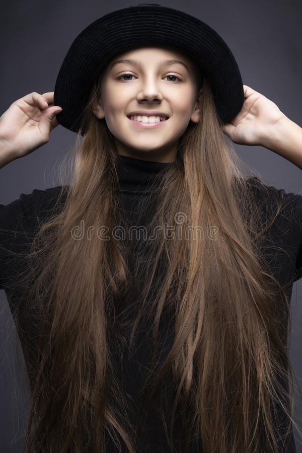 Funny portrait of a cute smiling teen girl wearing a dark turtleneck and hat. Gray background. Advertising, trendy and commercial stock images
