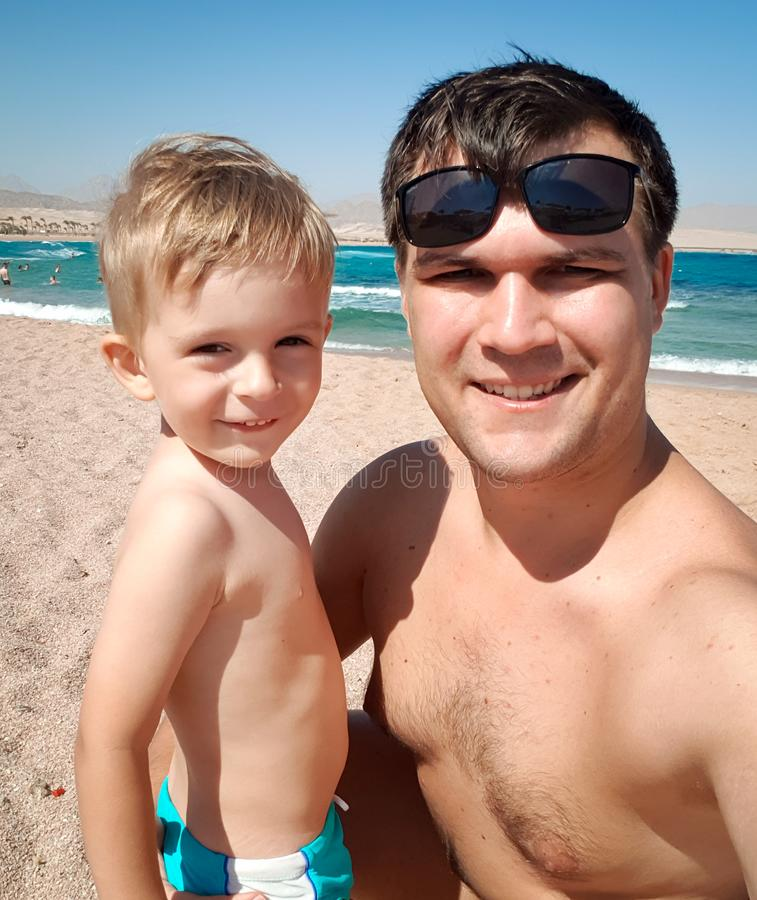 Funny portrait of young father making selfie image with his toddler son the sea beach at bright sunny. Family relaxing royalty free stock images