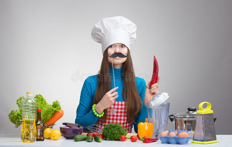 Funny portrait of a female chef with paper moustache and the red pepper stock photo