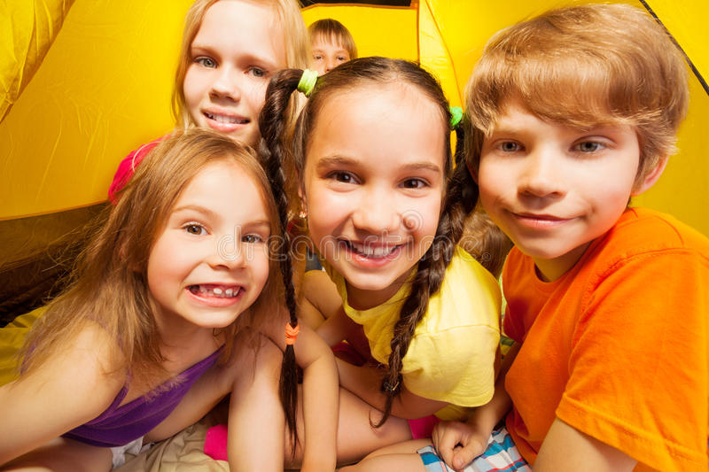 Funny portrait of five kids in a tent royalty free stock image