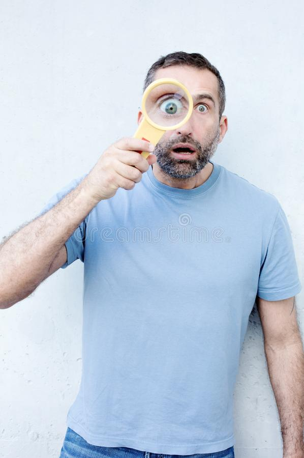 Handsome bearded man holding a magnifying glass royalty free stock images