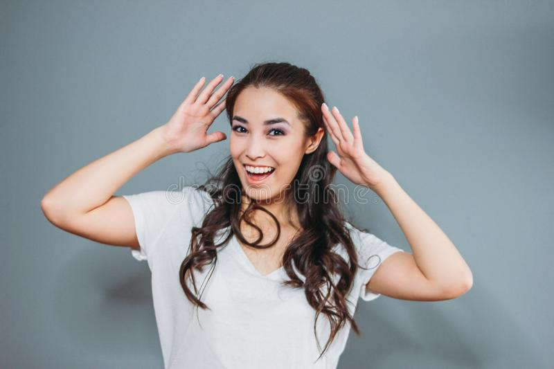 Funny portrait of happy asian young woman with dark long hair in white t-shirt on grey background royalty free stock photo