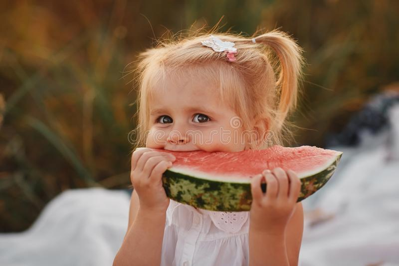 Funny portrait of an incredibly beautiful little girl eating watermelon on a hot summer day. portrait stock image
