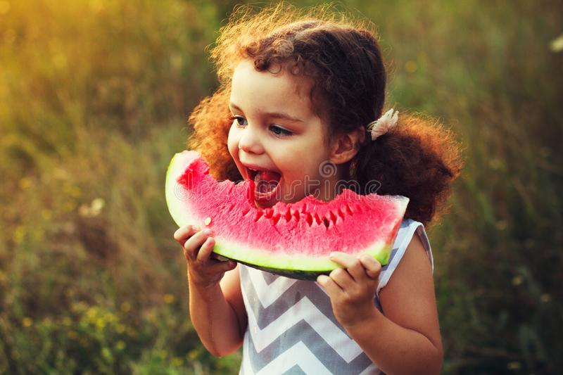 Funny portrait of an incredibly beautiful curly haired little girl eating watermelon, healthy fruit snack, adorable toddler child royalty free stock image
