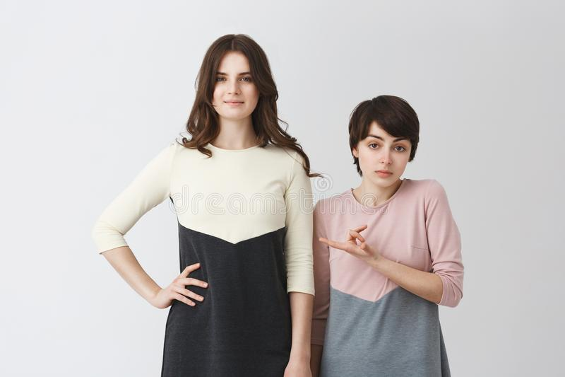 Funny portrait of lesbian pair of young student girls in matching clothes. Long-haired girl being taller than her short stock images