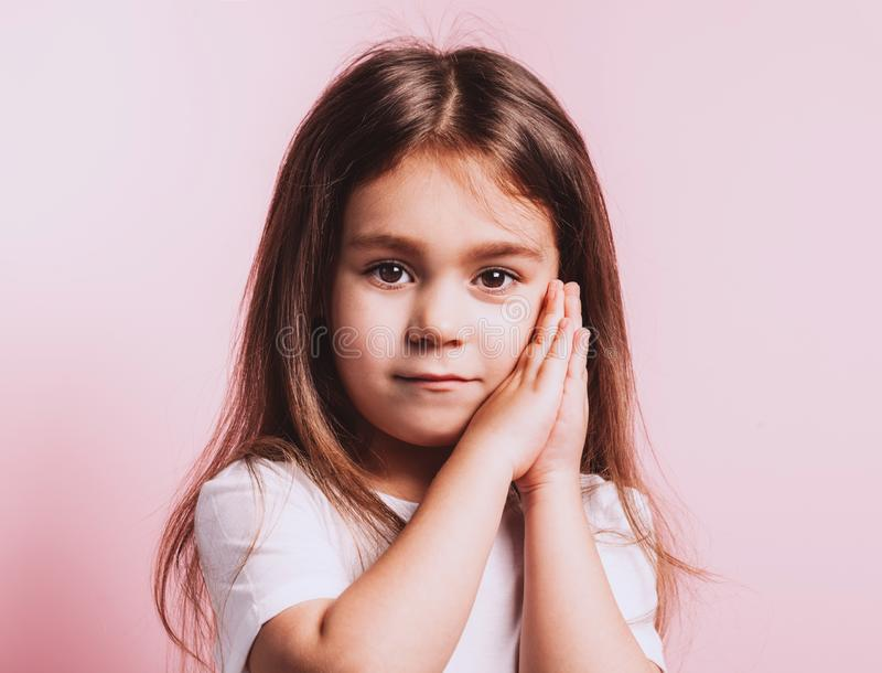 Funny portrait of little girl on pink background royalty free stock photography