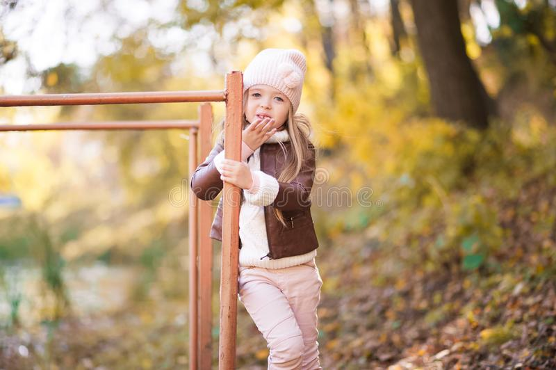 Funny portrait of a little girl. Little girl in a pink hat on a walk in the fall. Child girl in a jacket happily runs and collects. Little girl in a pink hat on royalty free stock photo