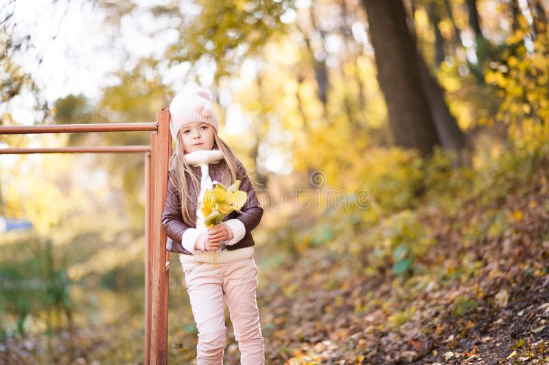 Funny portrait of a little girl. Little girl in a pink hat on a walk in the fall. Child girl in a jacket happily runs and collects. Little girl in a pink hat on royalty free stock photos