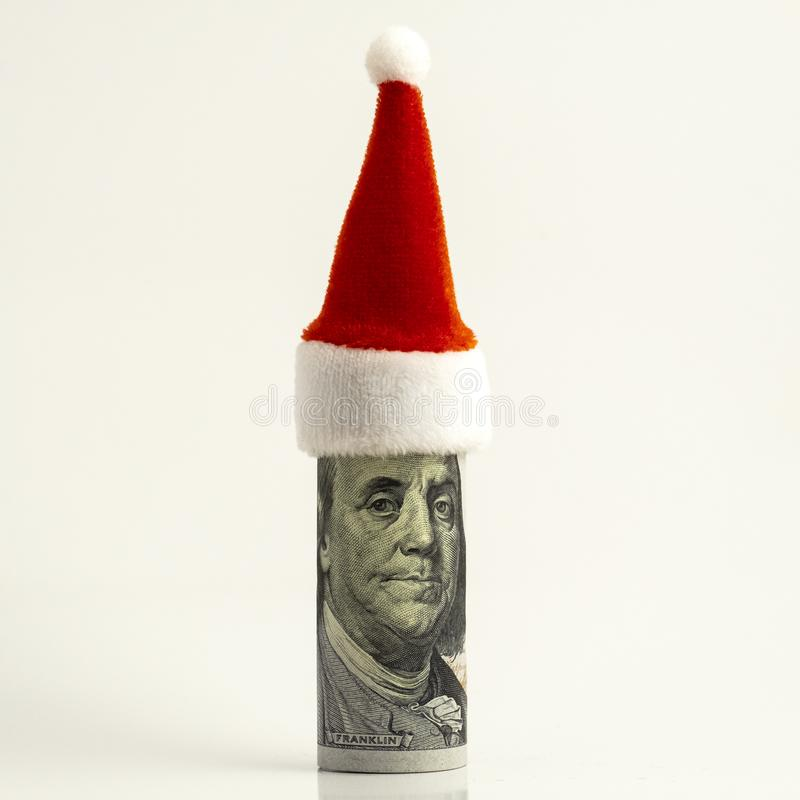 Funny portrait of President Franklin. The hundred-dollar bill is rolled up and the red Santa Claus hat at the top. Financial royalty free stock photography