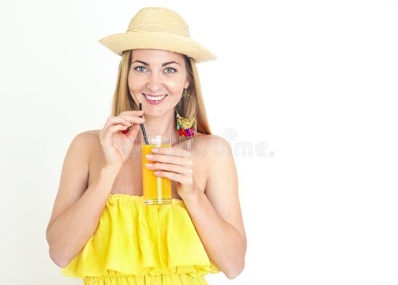 Smiling woman with hat on eyes drinking orange juice stock photos