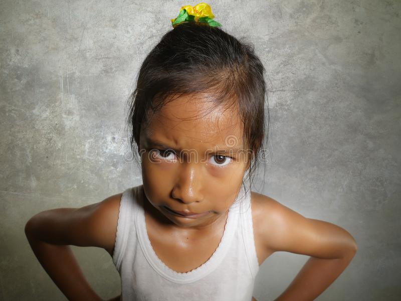 Funny portrait of sweet angry and mad 8 or 9 years old child looking upset to the camera feeling and unhappy isolated on. Grungy grey background in kid emotion stock image