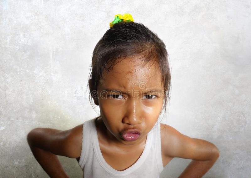 Funny portrait of sweet angry and mad 8 or 9 years old child looking upset to the camera feeling and unhappy isolated on. Grungy white background in kid emotion stock photography