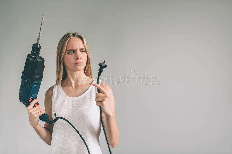 Funny portrait upset craftswoman. Blonde woman is wearing shirt isolated on white. Girl does not know how to use a drill stock photos