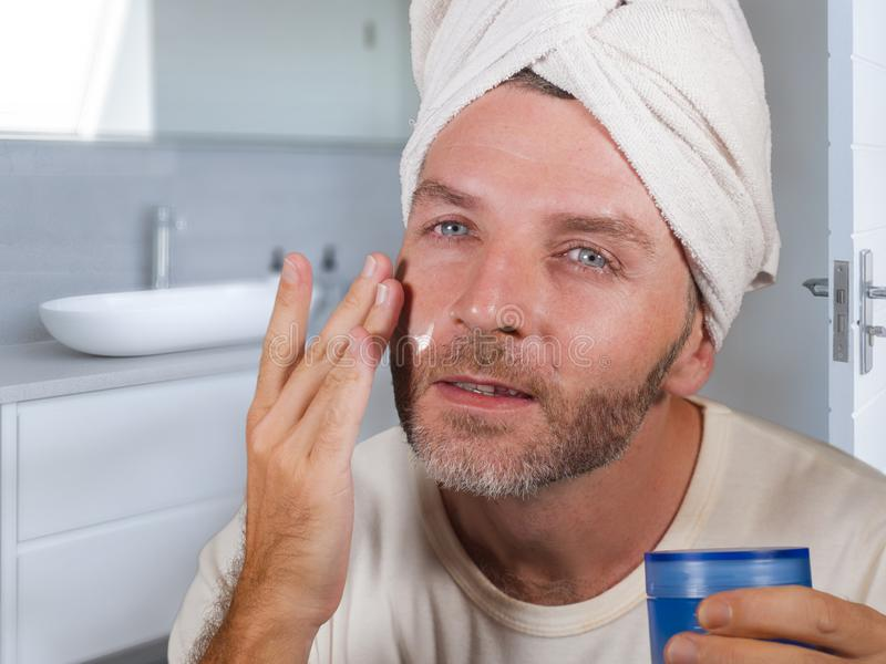 Funny portrait of young happy and attractive camp gay man in bathroom applying moisturizer facial cream with head wrapped in towel. Feeling confident in stock photos