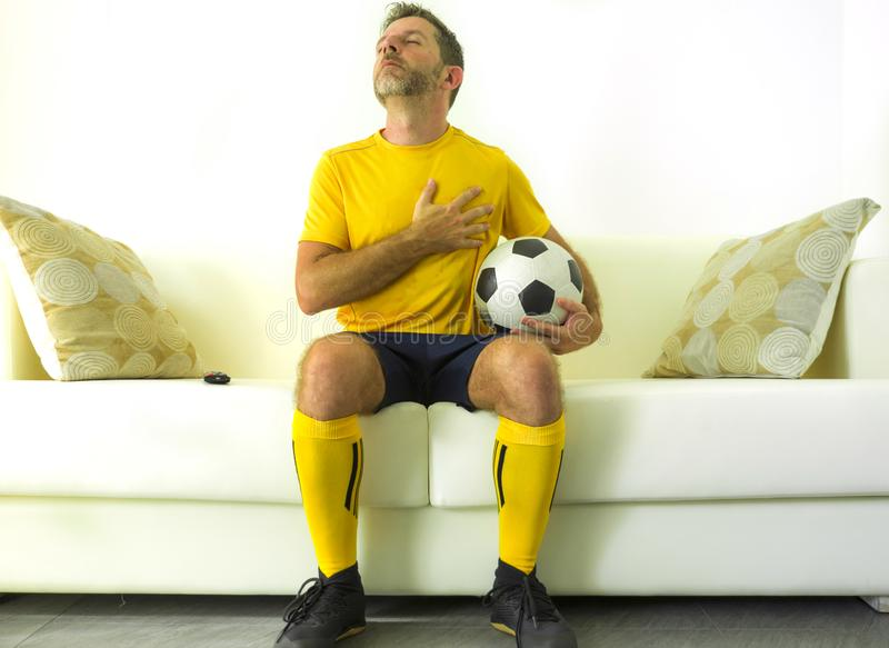 Funny portrait of young man in football team uniform watching soccer game on TV at home couch listening national anthem with hand stock images