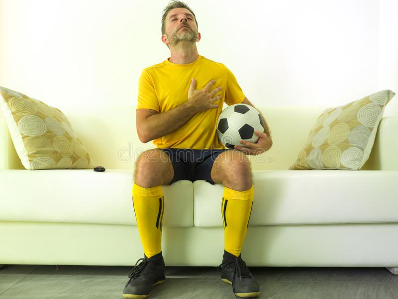 Funny portrait of young man in football team uniform watching soccer game on TV at home couch listening national anthem with hand royalty free stock photography
