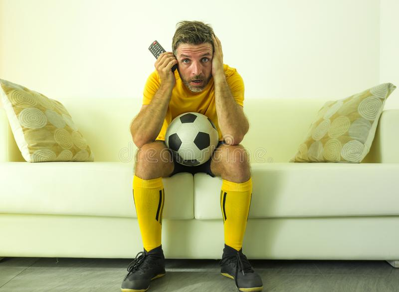 Funny portrait of young stressed and excited football fan man watching soccer game on TV at home couch dressed in team player. Uniform feeling the stress and royalty free stock photos