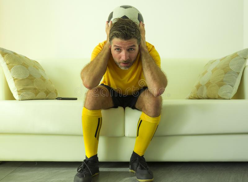 Funny portrait of young stressed and excited football fan man watching soccer game on TV at home couch dressed in team player. Uniform feeling the stress and stock photo
