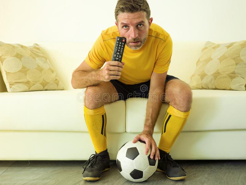 Funny portrait of young stressed and excited football fan man watching soccer game on TV at home couch dressed in team player. Uniform feeling the stress and stock photos