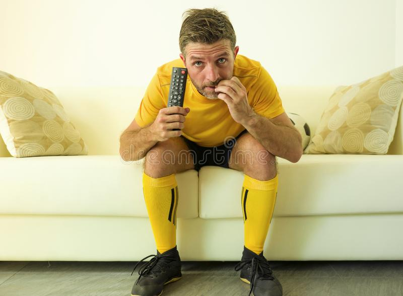 Funny portrait of young stressed and excited football fan man watching soccer game on TV at home couch dressed in team player stock photo