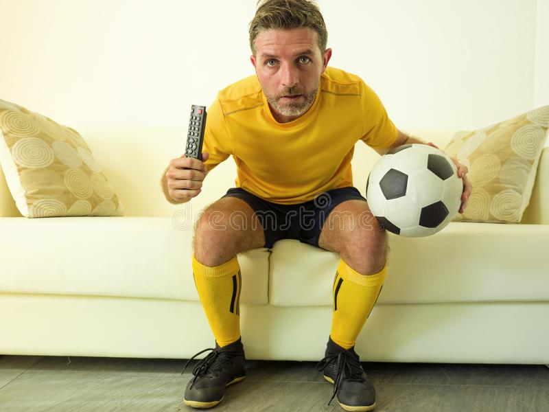 Funny portrait of young stressed and excited football fan man watching soccer game on TV at home couch dressed in team player stock images