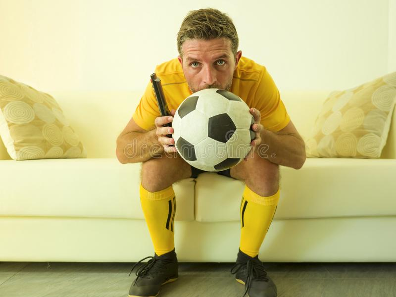 Funny portrait of young stressed and excited football fan man watching soccer game on TV at home couch dressed in team player royalty free stock photo