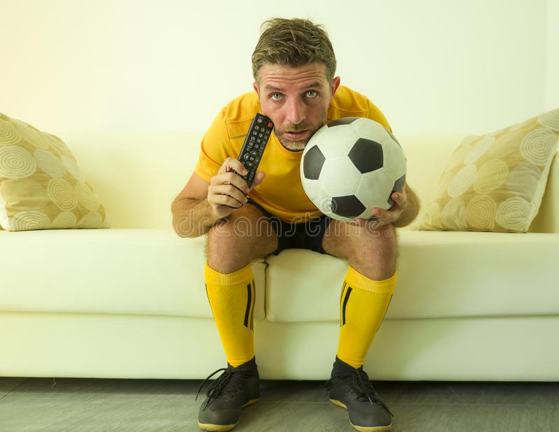 Funny portrait of young stressed and excited football fan man watching soccer game on TV at home couch dressed in team player royalty free stock images